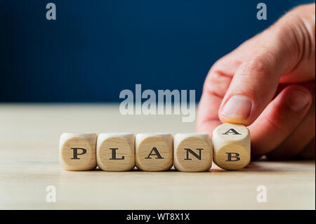 Plan A or B sign spelled on wooden dices with male hand turning the last dice. Over navy blue background.