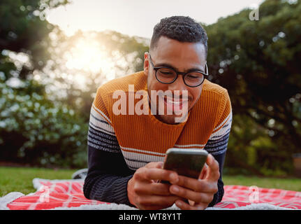 Portrait of an african smiling young man student wearing black eyeglasses relaxing in park using smart phone - college student using mobile in park - Stock Photo