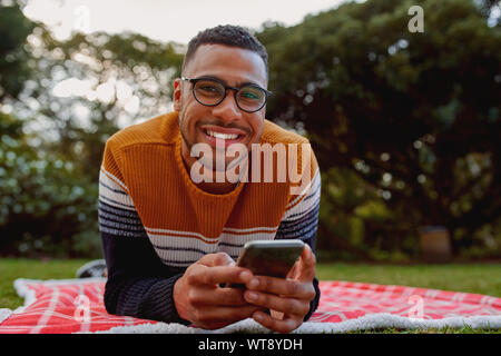 Portrait of a smiling african american young man lying on blanket in the park holding mobile phone in hand looking at camera smiling