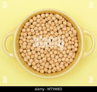 Directly Above Shot Of Soybeans In Bowl On Yellow Background - Stock Photo