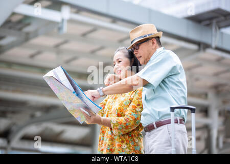 Senior Couple Looking At Map While Standing Against Building In city - Stock Photo