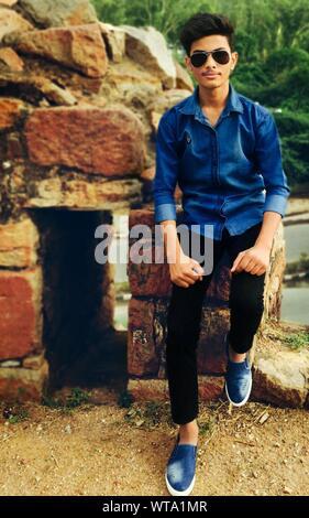Portrait Of Teenage Boy Posing While Sitting On Rock - Stock Photo