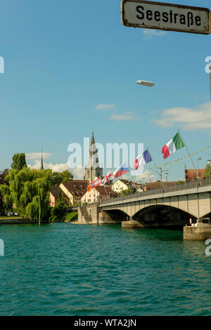 The Bridge over river Rhein, Rheinbruecke connecting the the old town and new part and Zeppelin in the sky,Konstanz, Germany - Stock Photo