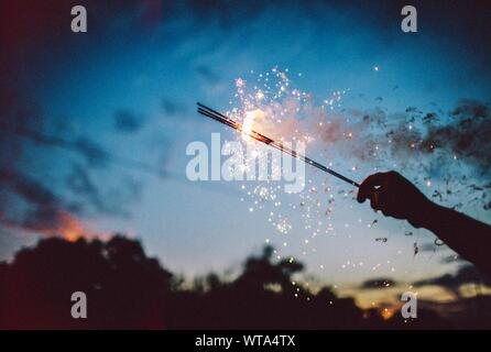 Close-up Of Silhouette Hand Holding Sparklers Against Sky At Night - Stock Photo