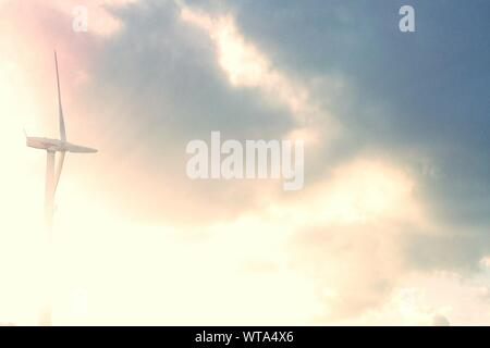 View Of Wind Turbine Against Cloudy Sky - Stock Photo