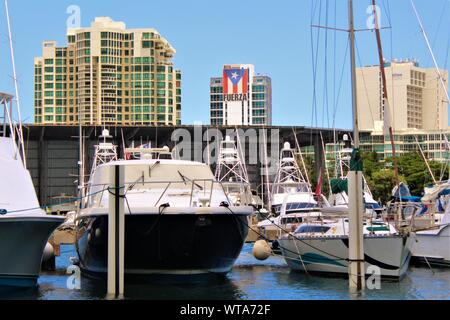 View from San Juan Bay Marina of moored boats in the foreground, and buildings in the background, including the headquarters of  'SOL Partners'. - Stock Photo