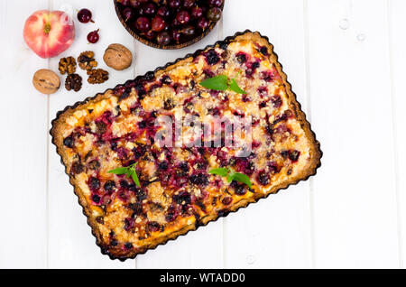 Homemade tart with berries, fruits and walnuts in shape on light background. Studio Photo - Stock Photo