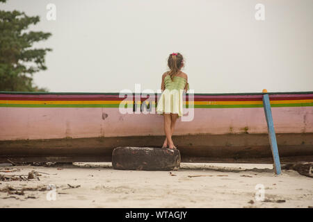 Girl in dress leaning over the fishing boat on the beach - Stock Photo