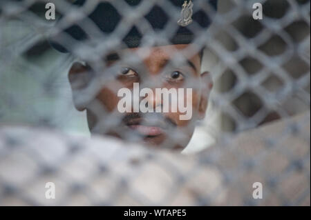Soldier behind fence on a street checkpoint in Srinagar - Stock Photo