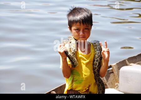 Portrait Of Cute Boy Holding Snake While Showing Peace Sign On Boat Against Lake - Stock Photo