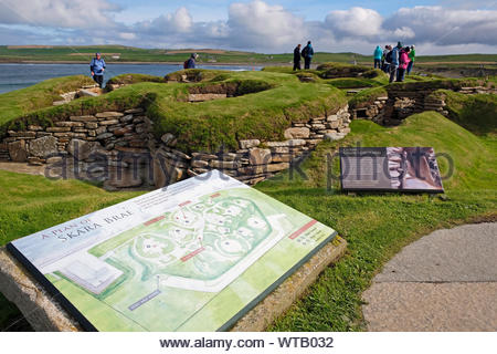 Tourists visiting Skara Brae, a stone-built Neolithic settlement, located on Mainland Orkney, Scotland - Stock Photo