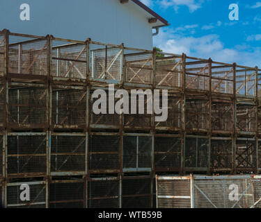 Old rusted transport boxes of metal grid stacked on a house wall - Stock Photo