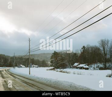 Power Lines On Snow Covered Field Against Sky - Stock Photo