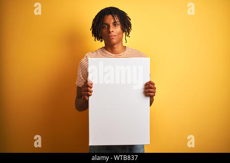 Afro american man with dreadlocks holding banner over isolated yellow background with a confident expression on smart face thinking serious - Stock Photo