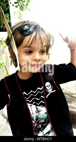 Smiling Boy Wearing Pirate Costume Standing Against Sky - Stock Photo