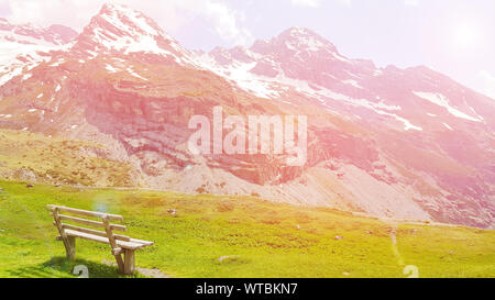 Beautiful natural landscape summer mountain landscape with colorful sunset over snowy mountain range dolomite italy with wooden bench and green meadow - Stock Photo