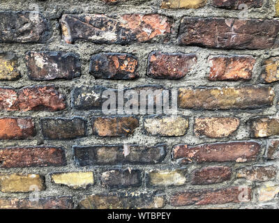 Antique red tempered brick wall. Part of the wall of an ancient building. - Stock Photo