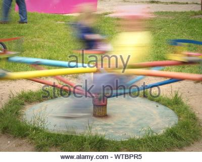 Blurred Motion Of People On Merry-go-round In Playground - Stock Photo