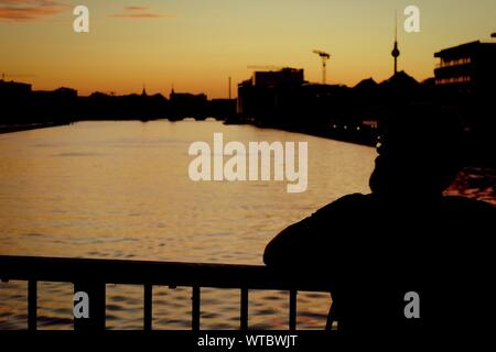 Silhouette Man Looking At City During Sunset - Stock Photo