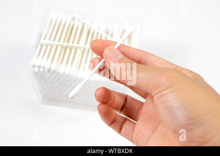 Hand holding cotton buds or cotton swab box in plastic transparent rectangular container and several cotton buds separately isolated on white backgrou - Stock Photo