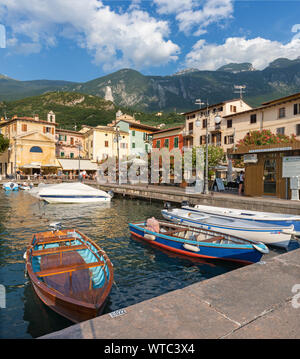 MALCESINE, ITALY - JUNE 13, 2019: The little harbor on the waterfront of Lago di Garda lake with the 2000 m high mountains in the background. - Stock Photo