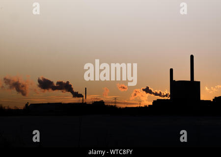Smoke Emitting From Silhouette Chimneys Against Sky During Sunset - Stock Photo