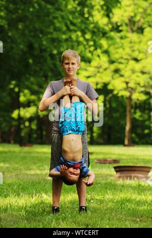 Portrait Of Teenage Boy Holding Brother Upside Down On Grassy Field - Stock Photo