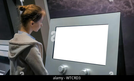 Woman looking at blank white display kiosk at exhibition - white screen concept - Stock Photo