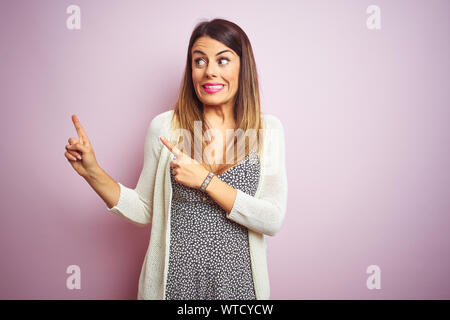 Young beautiful woman standing over pink isolated background Pointing aside worried and nervous with both hands, concerned and surprised expression - Stock Photo