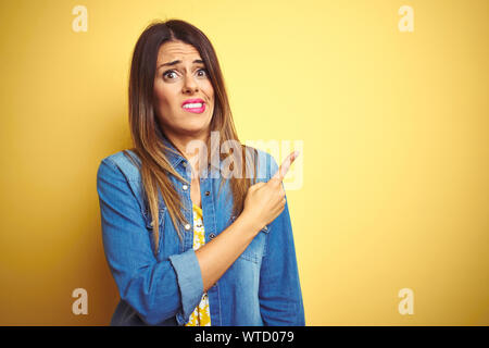 Young beautiful woman standing over yellow isolated background Pointing aside worried and nervous with forefinger, concerned and surprised expression - Stock Photo