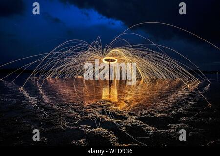 Man With Wire Wool On Shore Against Sky - Stock Photo