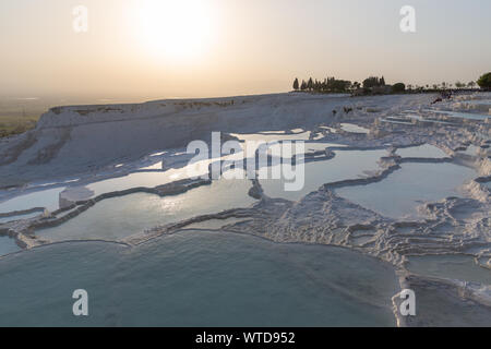 Sunset over travertines of Pamukkale - Cotton Castle - Cotton Palace Turkey with beautiful colors and reflections on water pools - Stock Photo