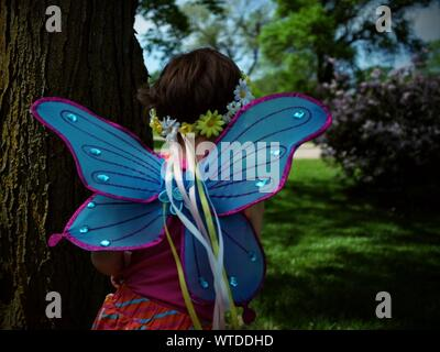 Rear View Of Girl Wearing Butterfly Costume By Tree Trunk - Stock Photo