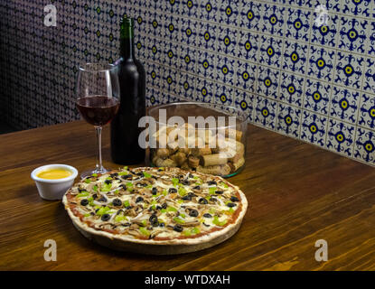 Homemade yummy pizza made of mushroom olives bell pepper and cheese served on a board on an old rustic wooden kitchen table surrounded by the fresh sa - Stock Photo