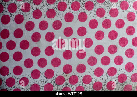 The texture of the old white fabric with red polka dots and black dots on a white background. A lot of red circles. - Stock Photo