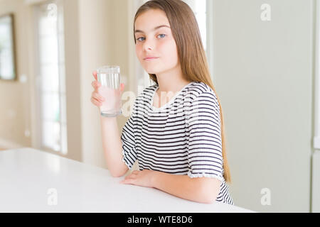 Beautiful young girl kid drinking a fresh glass of water with a confident expression on smart face thinking serious - Stock Photo