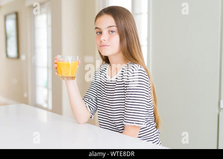 Beautiful young girl kid drinking a glass of fresh orange juice with a confident expression on smart face thinking serious - Stock Photo