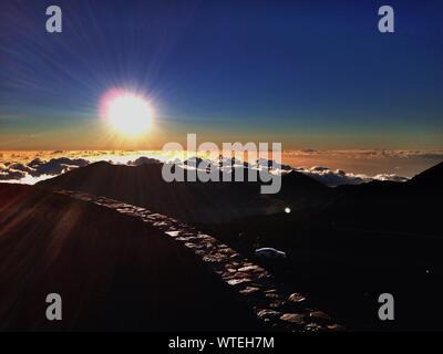 Bright Sun Shining Over Haleakala Observatory Against Blue Sky - Stock Photo