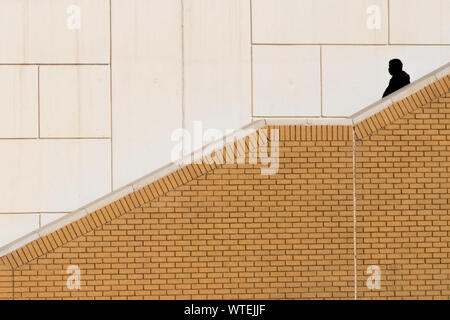 Silhouette Man Walking On Steps Against Wall - Stock Photo
