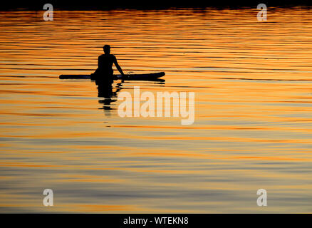 BAGENKOP, DENMARK, 17 JULY 2019: Silhouetted paddle boarder at peace, watching the colorful setting sun from his board on the sea. Relaxation, serene. - Stock Photo