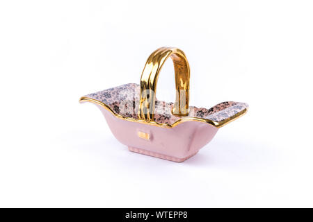 pink porcelain basket with golden handle and floral motive with black flowers on pure white background - Stock Photo