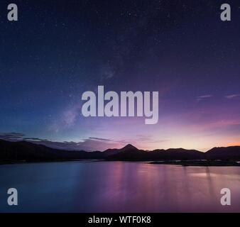 Long Exposure Shot Of Milky Way Over Majestic Mountain Lake - Stock Photo