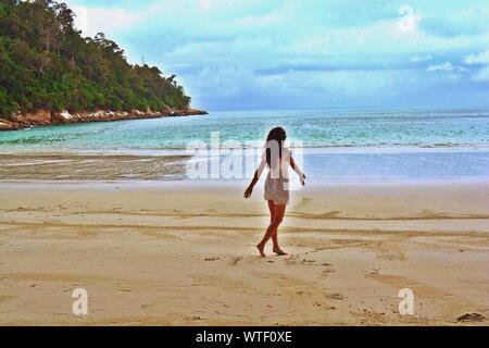 Full Length Rear View Of Woman Enjoying Wind At Beach - Stock Photo