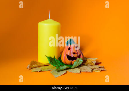 Composition with decorative ceramic Halloween pumpkin jack-o-lantern on dry autumn leaves and yellow candle - Stock Photo