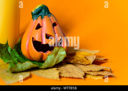 Close-up of decorative ceramic Halloween pumpkin jack-o-lantern on dry autumn leaves and yellow candle. - Stock Photo