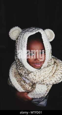High Angle Portrait Of Smiling Boy Wearing Sweater Against Black Background - Stock Photo