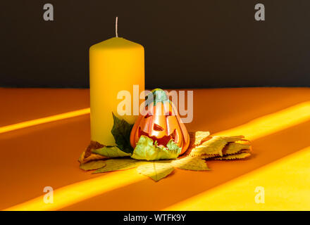 Ceramic Halloween pumpkin jack-o-lantern on dry autumn leaves, yellow candle and strong shadows - Stock Photo