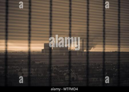 Smoke Emitting From Chimneys Against Sky During Sunset Seen Through Window - Stock Photo