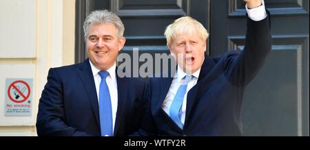 Boris Johnson shakes hands with Chairman of Conservative Party Brandon Lewis as he arrives at Conservative party HQ in Westminster on July 23, 2019. - Stock Photo