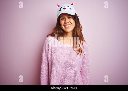 Young beautiful woman wearing funny cat cap standing over pink isolated background with a happy and cool smile on face. Lucky person. - Stock Photo